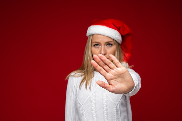 Kerst concept foto van een serieuze dame in kerstmuts haar arm naar voren als een stopbord uitbreiden. vakantie concept
