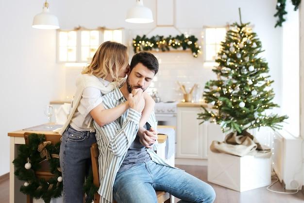 Kerst concept, man en vrouw verliefd knuffel en kus in de ingerichte lichte keuken thuis