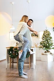 Kerst concept, man en vrouw verliefd met plezier en dansen in de ingerichte keuken thuis