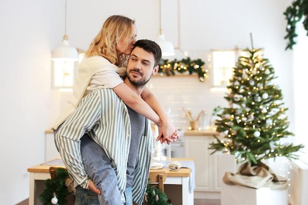 Kerst concept, man en vrouw verliefd met plezier en kussen in ingerichte keuken thuis