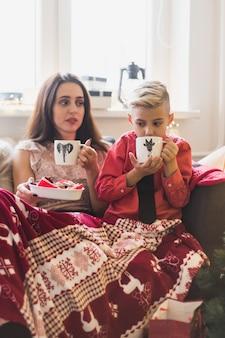 Kerst concept met vrouw en jongen het drinken van thee