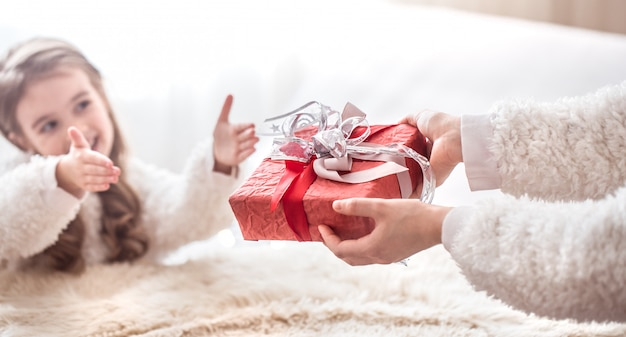 Kerst concept, moeder geeft een cadeau aan een kleine schattige dochter, een plek om te sms'en op een lichte achtergrond