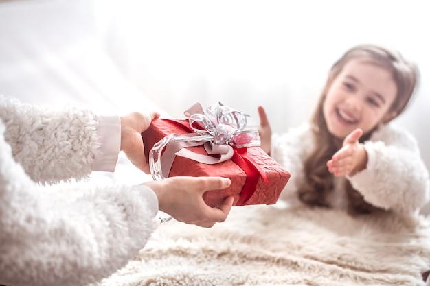 Kerst concept, moeder geeft een cadeau aan een kleine schattige dochter, een plek om te sms'en op een lichte muur