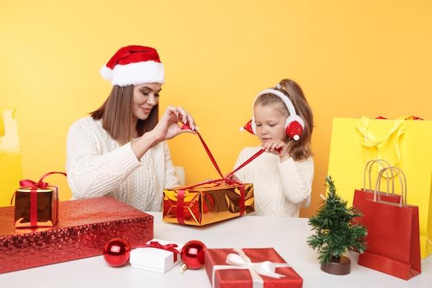 Kerst concept. moeder met meisje op vakantie. samen cadeaus uitpakken.
