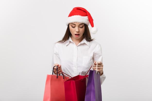 Kerst concept mooie blanke zakenvrouw schokkend met cadeau in boodschappentas