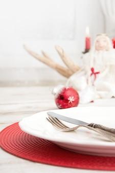 Kerst couvert met wit servies, bestek, zilverwerk en rode decoraties
