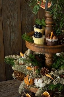 Kerst cupcakes gemaakt van witte en donkere chocolade, versierd met bessen, noten en plakjes mandarijnen.