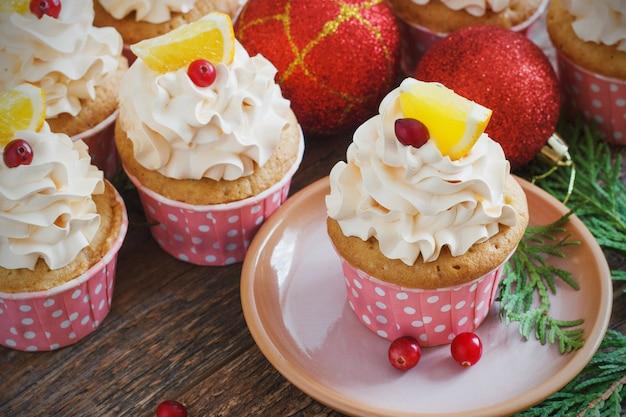 Kerst cupcakes met slagroom topping en veenbessen, sinaasappel. feestelijk eten dessert.