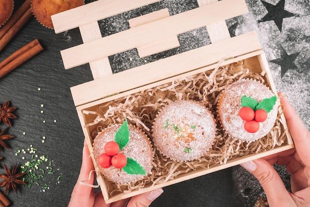 Kerst cupcakes versierd met maretak in een houten kist