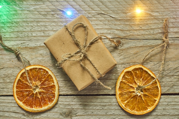 Kerst decor. gedroogde stukjes sinaasappel en geschenkdoos in ambachtelijk papier, bovenaanzicht, minimale platlegging