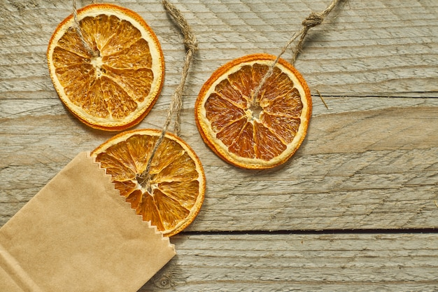 Kerst decor. gedroogde stukjes sinaasappel in ambachtelijke papieren verpakking, bovenaanzicht, minimale platlegging