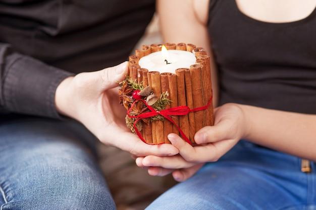 Kerst decor. handen van vader en dochterholdings brandende kaars. gelukkig gezin