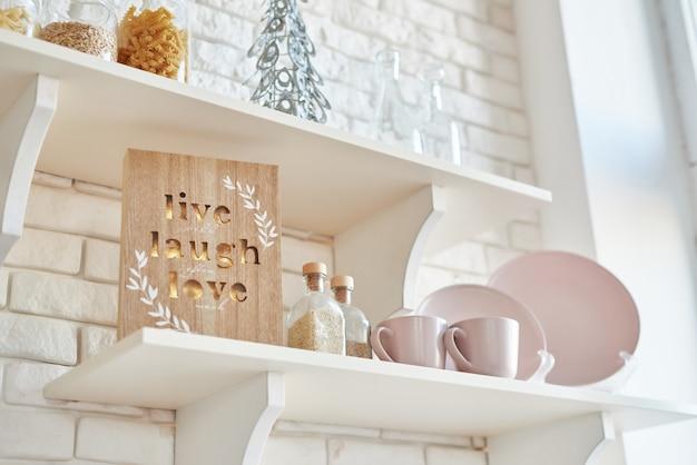 Kerst decor in keuken. kerst servies. kerst kookgerei. licht interieur van de new year's keuken. nieuwjaarskaartsjabloon. witte kleuren keuken. kerstboom in de keuken.