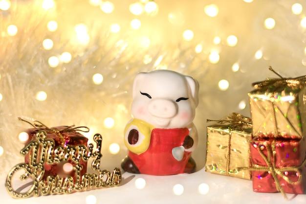 Kerst decor. keramisch varken, symbool van het nieuwe jaar 2019 op chinese kalender bokeh achtergrond