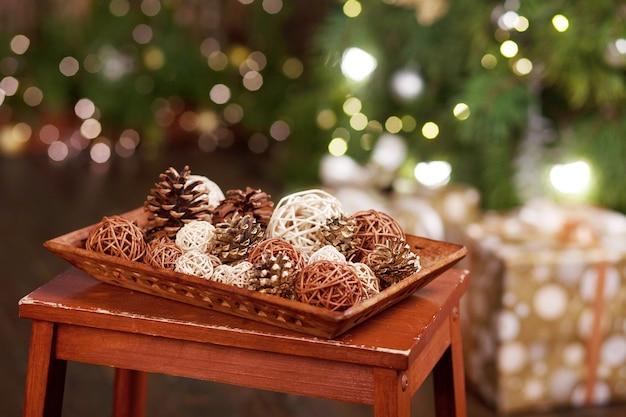 Kerst decor. pijnboomstoten en roterende ballen op een houten dienblad op kerstverlichting. kerstvakantie. kopieer ruimte