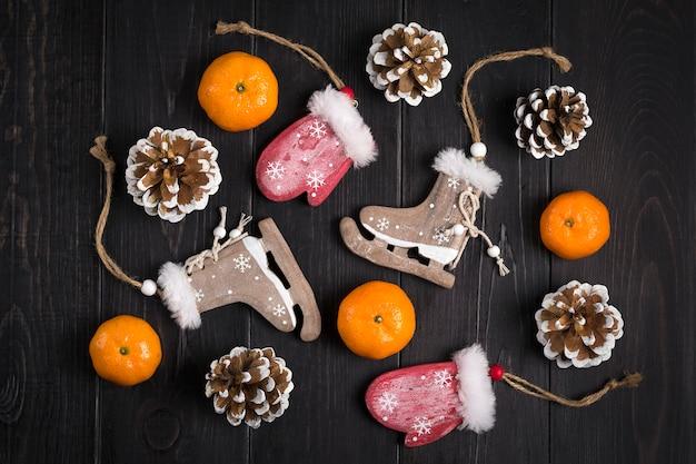 Kerst decor. schaatsen, wanten, sneeuwvlokken, mandarijnen, kegels op houten achtergrond flat lag