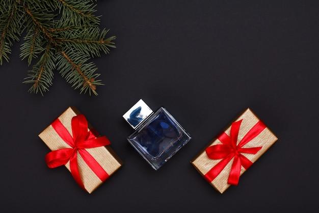 Kerst decoratie. geschenkdozen, fles parfum en natuurlijke dennenboomtak op zwarte achtergrond. bovenaanzicht. kerst wenskaart concept.