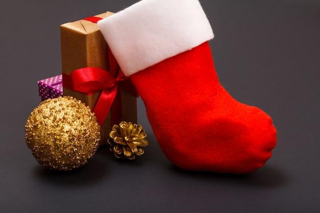 Kerst decoratie. geschenkdozen, santa's laars, speelgoedbal en natuurlijke kegel op zwarte achtergrond. kerst wenskaart concept.