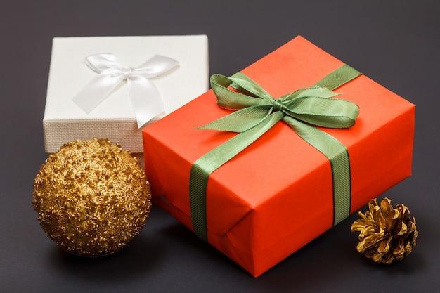 Kerst decoratie. geschenkdozen, speelgoedbal en natuurlijke kegel op zwarte achtergrond. kerst wenskaart concept.