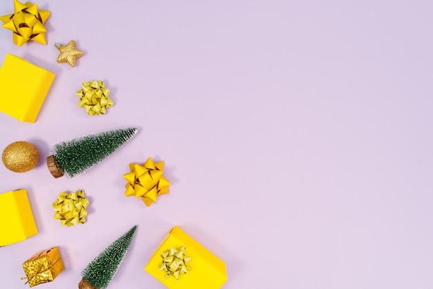 Kerst decoratie. geschenken, gele en gouden decoraties op paarse achtergrond.
