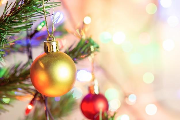 Kerst decoratie. hangende gouden ballen op pijnboomtakken kerstboomslinger en ornamenten over abstracte bokehachtergrond met copyspace