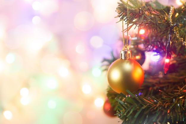 Kerst decoratie. het hangen van gouden ballen op de kerstboomslinger en ornamenten van pijnboomtakken over samenvatting bokeh met exemplaarruimte