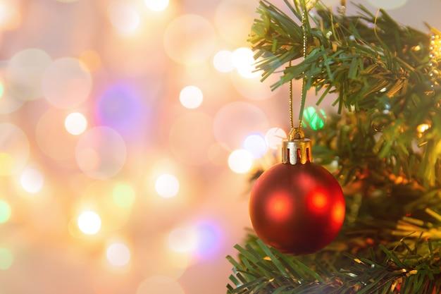 Kerst decoratie. het hangen van rode ballen op de kerstboomslinger en ornamenten van pijnboomtakken over samenvatting bokeh met exemplaarruimte