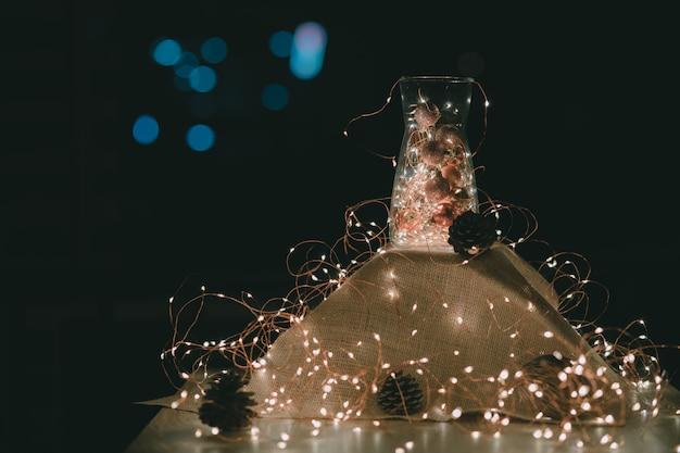 Kerst decoratie. kerstverlichting en kerstversieringen in een glazen pot met warme lichten gloeien omringd met een reeks lichten