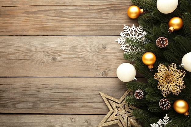 Kerst decoratie. sparrentak met gouden en zilveren ballen, kerstmisbloem en ster op grijs