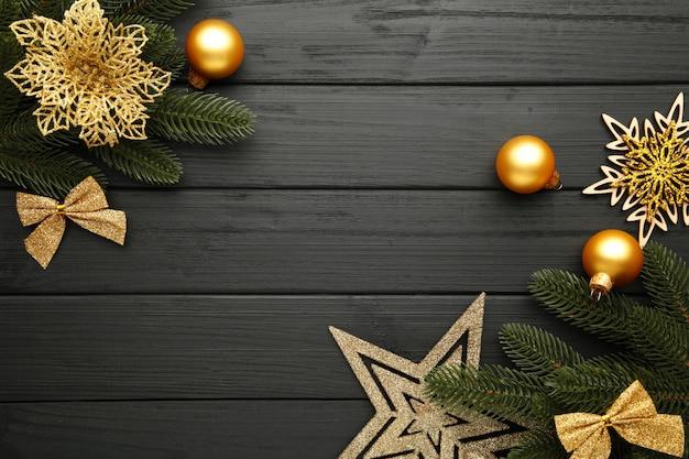 Kerst decoratie. sparrentak met gouden ster, kerstmisbloem en ballen op zwarte
