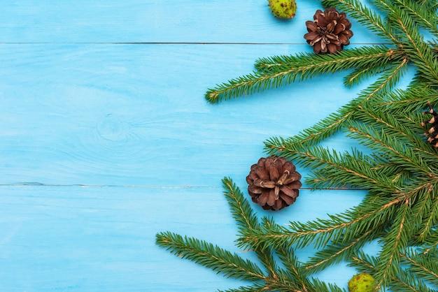 Kerst dennennaalden met dennenappels op een lichtblauwe achtergrond. kopieer ruimte.