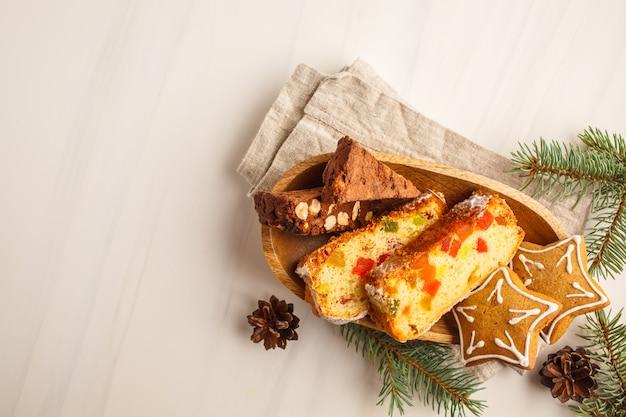 Kerst desserts van verschillende landen (panforte, koekjes en kerst brood) op een witte achtergrond.