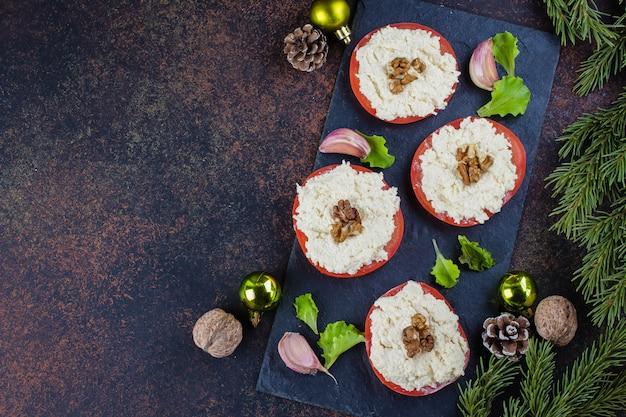 Kerst diner tabel instelling. heerlijke snacktomaat met geraspte kaas met knoflook op donkere steenlijst. bovenaanzicht, kopie ruimte. feestelijke decoratie, dennentak
