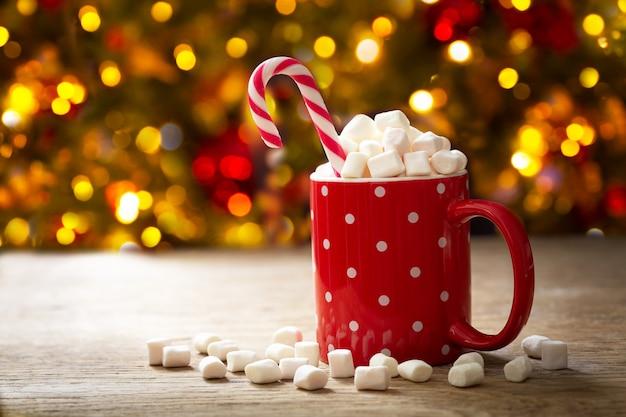 Kerst drankje. kop warme chocolademelk met marshmallows en rode zuurstok op feestelijke achtergrond