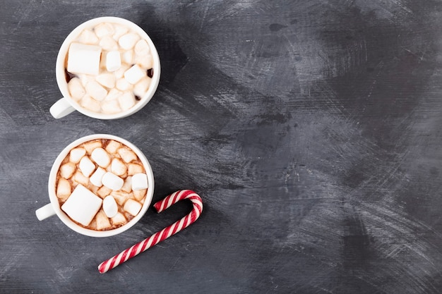 Kerst drankje. twee kopjes warme chocolademelk met marshmallow en zuurstok