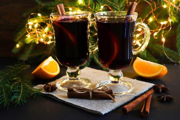 Kerst drankjes. twee glazen glühwein, kaneel en sinaasappels op feestelijke kerstmis