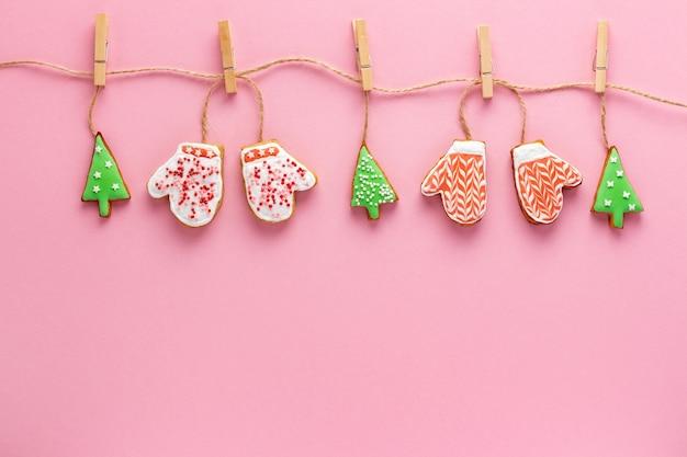 Kerst eco-vriendelijke slinger met versierde peperkoek op roze achtergrond