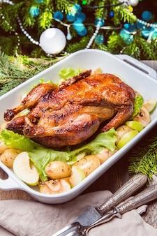 Kerst eend met appels en kruiden in witte pan met wintervakantie decoraties
