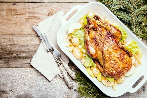 Kerst eend met appels en kruiden in witte pan over houten oppervlak, bovenaanzicht