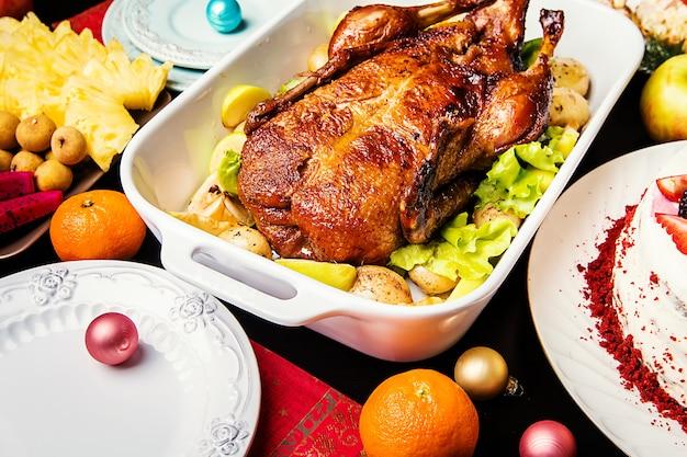 Kerst eend met appels en kruiden in witte pan over houten