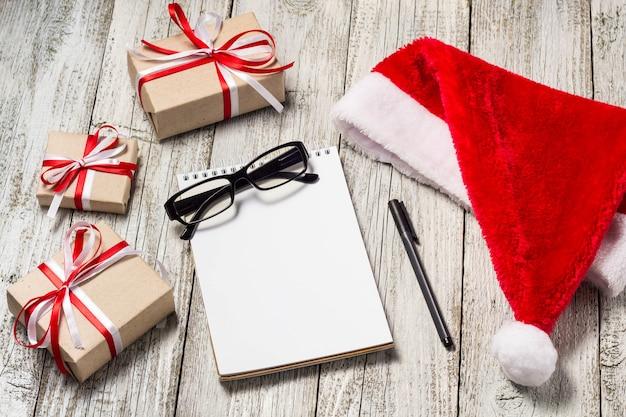 Kerst- en kantoorartikelen met kopie ruimte kerstmuts kladblok pen bril en versierde geschenkdozen