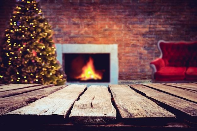 Kerst en nieuwjaar achtergrond met lege donkere houten dek tafel over kerstboom en wazig licht bokeh. leeg scherm voor product montage. rustieke vintage kerstmis achtergrond.