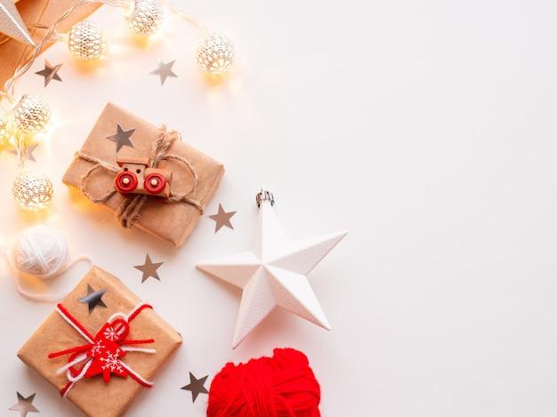 Kerst- en nieuwjaars verpakte doe-het-zelfcadeaus in ambachtelijk papier. geschenk gebonden met rustieke draad met speelgoed trein als decoratie.