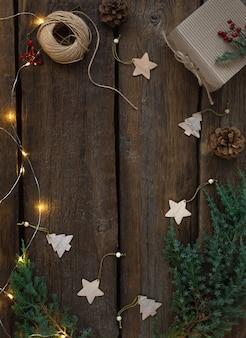 Kerst- en nieuwjaarsbordframe met dennentakken, een brandende slinger, geschenkdoos, houten speelgoed. rustieke houten achtergrond, kopie ruimte.