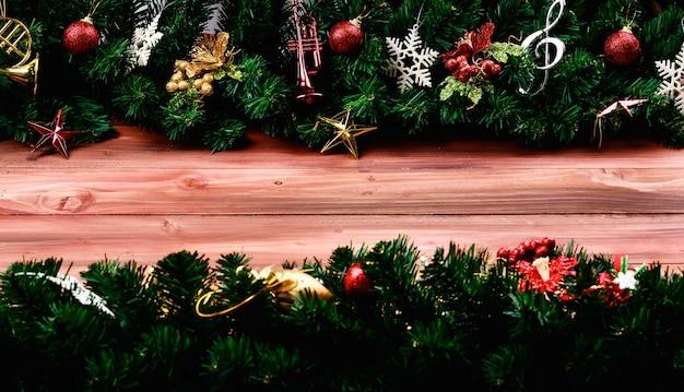 Kerst- en nieuwjaarsdecoratierand op natuurlijke houten bord brede kopieerruimte in het midden. feestelijke ornamenten met pijnboomtakken en kunstmatig muziekinstrument.