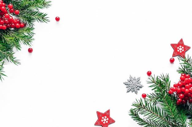 Kerst- en nieuwjaarskaart met fir takken en decor op de witte achtergrond.