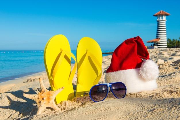 Kerst- en nieuwjaarsvakantie aan zee. kerstmuts, sandalen, zonnebril op zandstrand