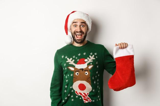 Kerst- en wintervakantie concept. gelukkige man kreeg een cadeau in kerstsok, keek opgewonden, staande in kerstmuts tegen een witte achtergrond.