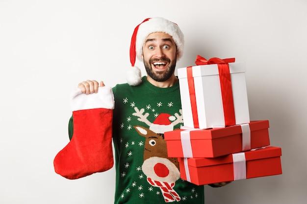 Kerst- en wintervakantie concept. opgewonden man met kerstsokken en geschenkdozen, nieuwjaar vieren, cadeautjes brengen onder de boom, staande op een witte achtergrond