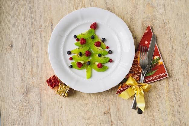 Kerst eten voor kinderen. witte schotel met kerstboom gemaakt van kiwi, frambozen, bosbes en bosbes op houten tafel. hoge kwaliteit foto